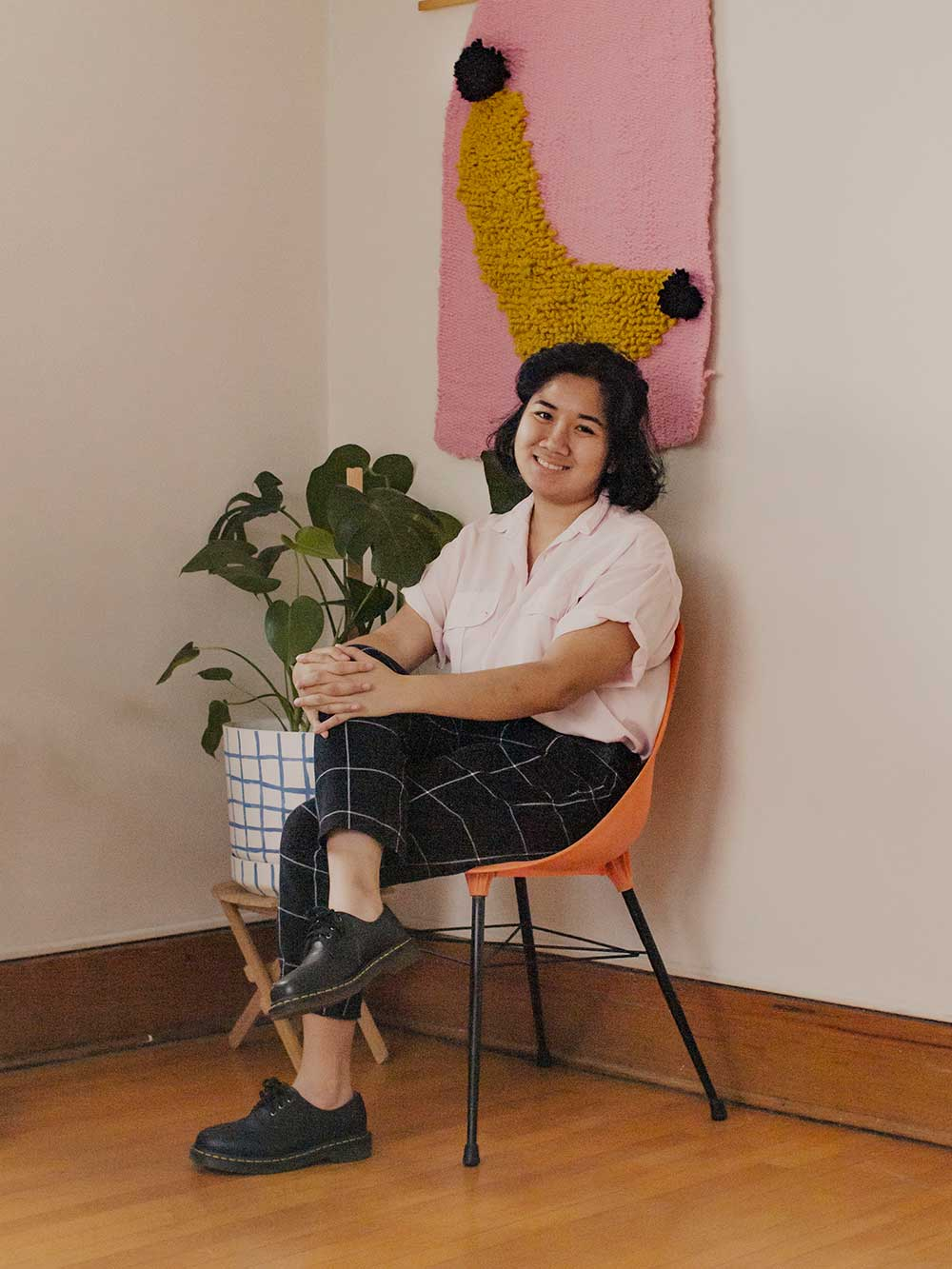 Anh Tran sitting in chair by houseplant